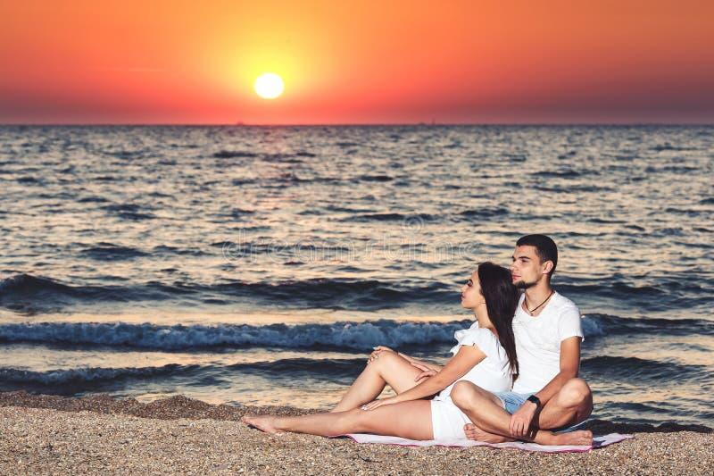 Μια νεολαία συνδέει ερωτευμένο στηρίζεται και απολαμβάνει την ανατολή στην παραλία στοκ εικόνα