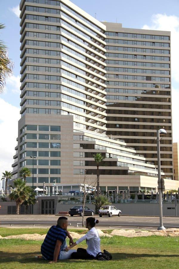 Μια νεολαία συνδέει στο υπόβαθρο ενός ξενοδοχείου στην προκυμαία του Τελ Αβίβ στοκ εικόνες