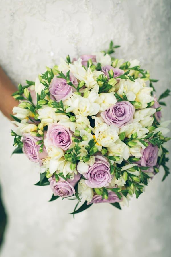 Μια νύφη που κρατά μια όμορφη ανθοδέσμη των πορφυρών και άσπρων λουλουδιών στοκ εικόνα