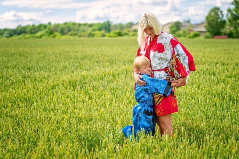 Μια ξανθή γυναίκα με το γιο της, που ντύθηκε στο κιμονό, αγκαλίασε στοργικά τον τομέα των δημητριακών στοκ φωτογραφίες