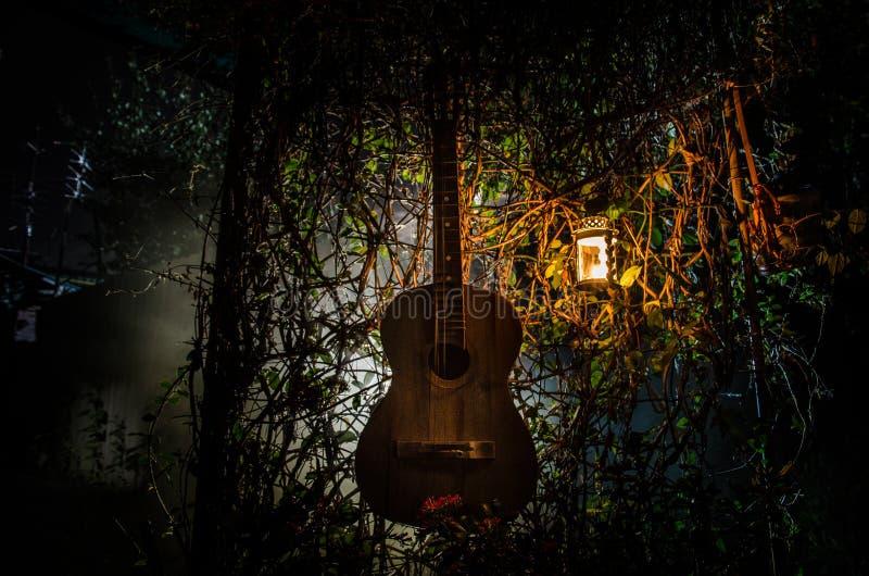 Μια ξύλινη ακουστική κιθάρα είναι ενάντια σε έναν κατασκευασμένο τοίχο grunge Το δωμάτιο είναι σκοτεινό με ένα επίκεντρο για το c στοκ φωτογραφίες