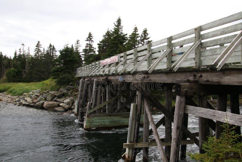 Μια ξύλινη γέφυρα που διασχίζει έναν επικίνδυνα γρήγορο ποταμό στοκ εικόνα