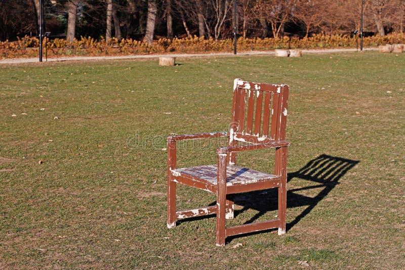 Μια ξύλινη καρέκλα στέκεται στην πράσινη χλόη στοκ εικόνα