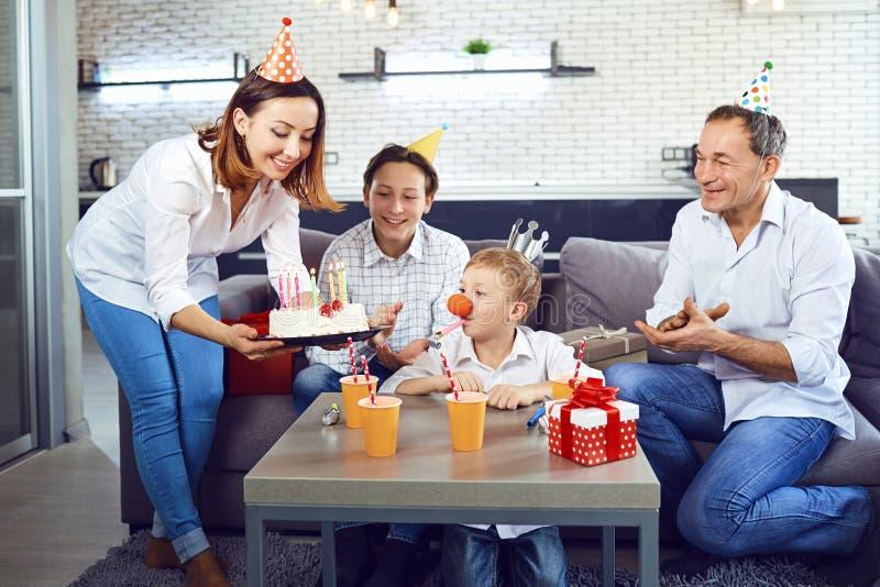 Μια οικογένεια με ένα κέικ κεριών γιορτάζει μια γιορτή γενεθλίων στοκ εικόνα
