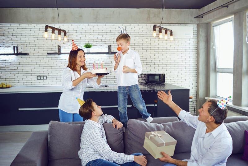 Μια οικογένεια με ένα κέικ κεριών γιορτάζει μια γιορτή γενεθλίων στοκ φωτογραφία