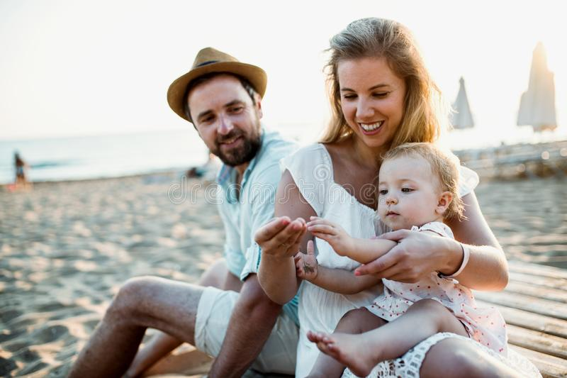 Μια οικογένεια με μια συνεδρίαση κοριτσιών μικρών παιδιών στην παραλία άμμου στις καλοκαιρινές διακοπές στοκ φωτογραφία με δικαίωμα ελεύθερης χρήσης