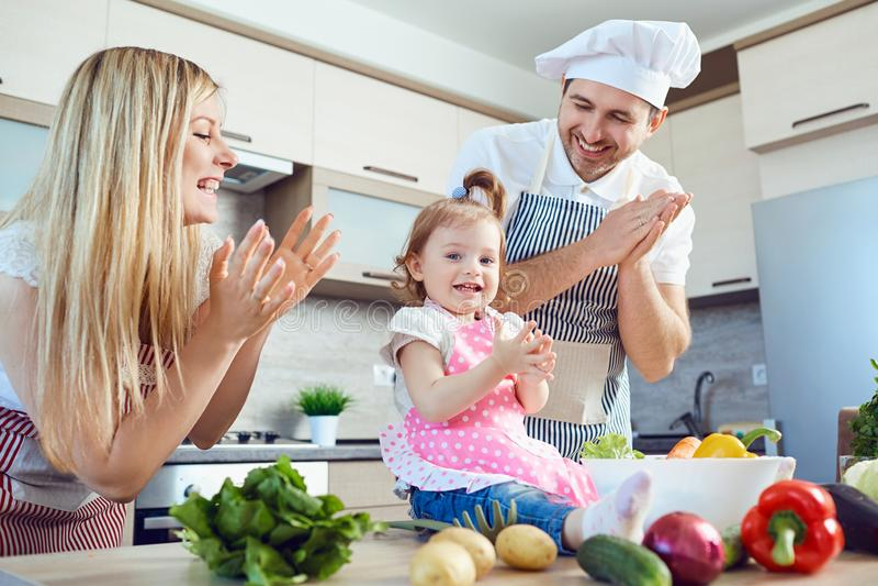 Μια οικογένεια προετοιμάζει τα τρόφιμα από τα λαχανικά στην κουζίνα στοκ φωτογραφία με δικαίωμα ελεύθερης χρήσης