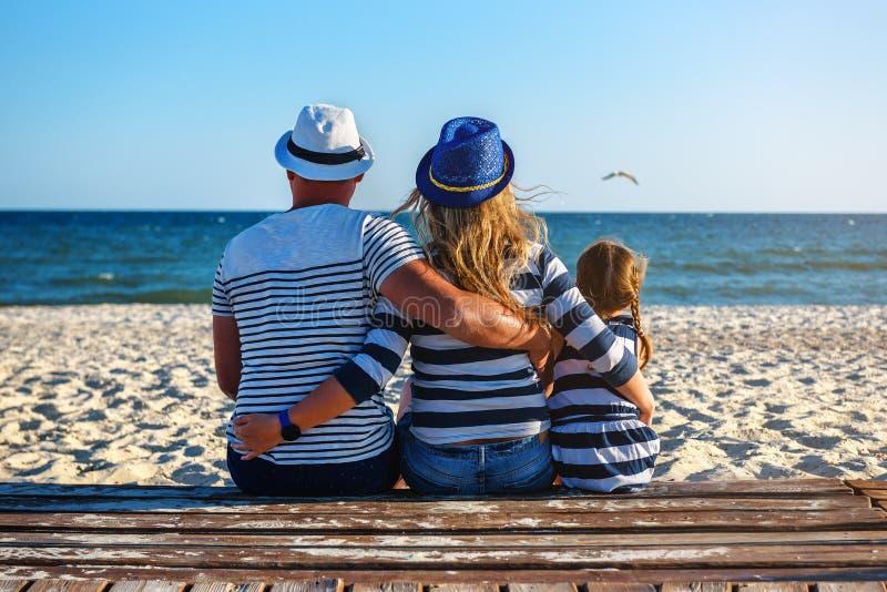 Μια οικογένεια στα ριγωτά ενδύματα που κάθεται στην παραλία στοκ φωτογραφία με δικαίωμα ελεύθερης χρήσης