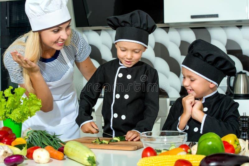 Μια οικογένεια των μαγείρων κατανάλωση υγιής Η ευτυχή οικογενειακά μητέρα και τα παιδιά προετοιμάζουν τη φυτική σαλάτα στην κουζί στοκ εικόνα με δικαίωμα ελεύθερης χρήσης