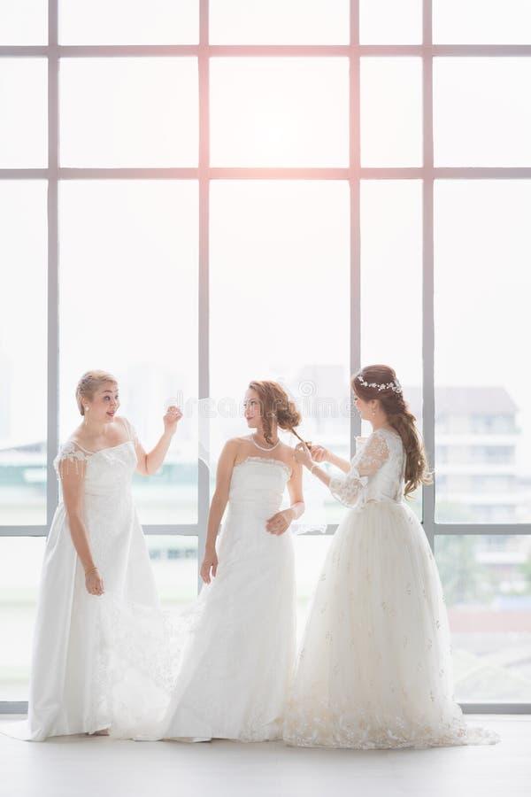 Μια ομάδα από όμορφες νύφες τακτοποιούν το φόρεμά τους στοκ εικόνα