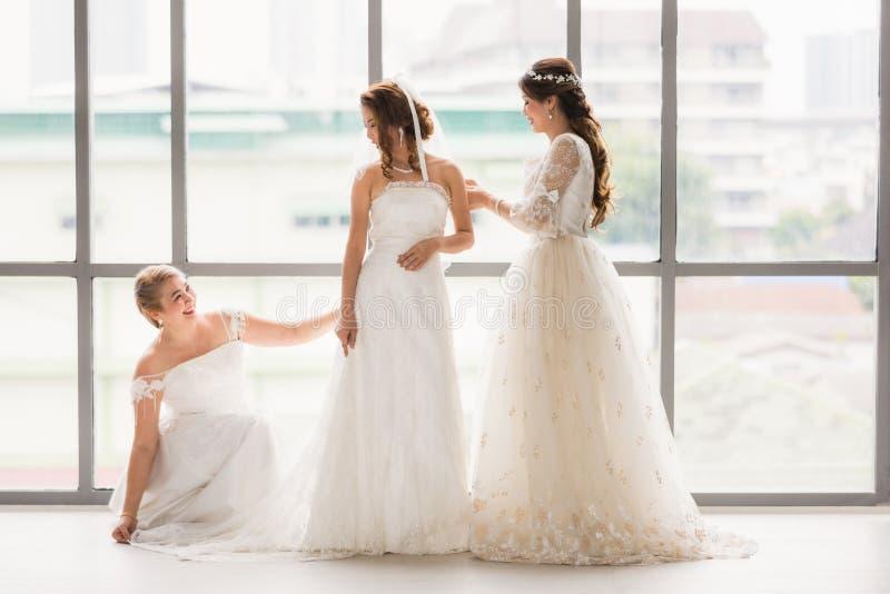 Μια ομάδα από όμορφες νύφες τακτοποιούν το φόρεμά τους στοκ εικόνες