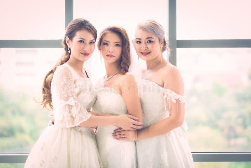 Μια ομάδα από όμορφες νύφες τακτοποιούν το φόρεμά τους στοκ φωτογραφία