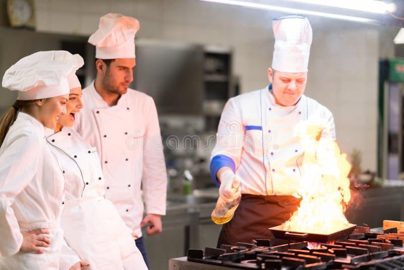 Μια ομάδα αρχιμαγείρων που προετοιμάζουν το εύγευστο γεύμα στο υψηλό εστιατόριο πολυτέλειας στοκ εικόνες με δικαίωμα ελεύθερης χρήσης