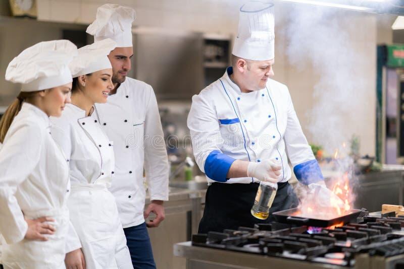 Μια ομάδα αρχιμαγείρων που προετοιμάζουν το εύγευστο γεύμα στο υψηλό εστιατόριο πολυτέλειας στοκ εικόνες