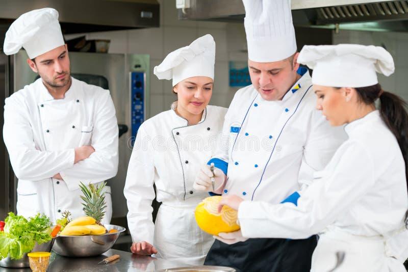 Μια ομάδα αρχιμαγείρων που προετοιμάζουν το εύγευστο γεύμα στο υψηλό εστιατόριο πολυτέλειας στοκ φωτογραφίες με δικαίωμα ελεύθερης χρήσης