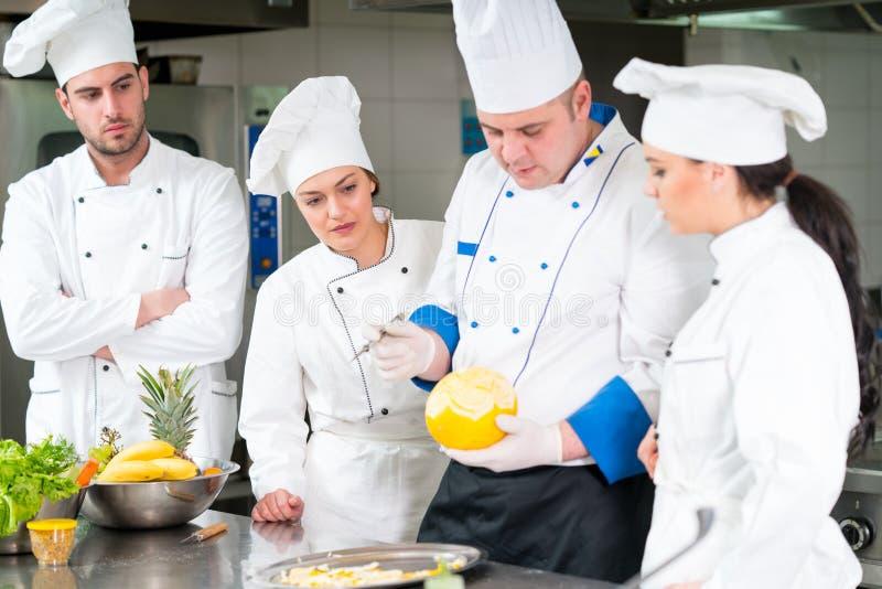Μια ομάδα αρχιμαγείρων που προετοιμάζουν το εύγευστο γεύμα στο υψηλό εστιατόριο πολυτέλειας στοκ φωτογραφία με δικαίωμα ελεύθερης χρήσης