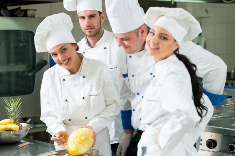 Μια ομάδα αρχιμαγείρων που προετοιμάζουν το εύγευστο γεύμα στο υψηλό εστιατόριο πολυτέλειας στοκ εικόνα με δικαίωμα ελεύθερης χρήσης