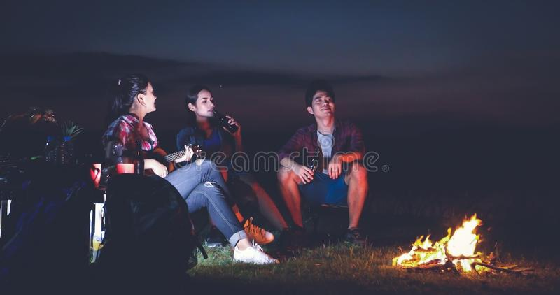 Μια ομάδα ασιατικής κατανάλωσης τουριστών φίλων και κιθάρας παιχνιδιού μαζί με την ευτυχία το καλοκαίρι ενώ έχοντας τη στρατοπέδε στοκ εικόνες