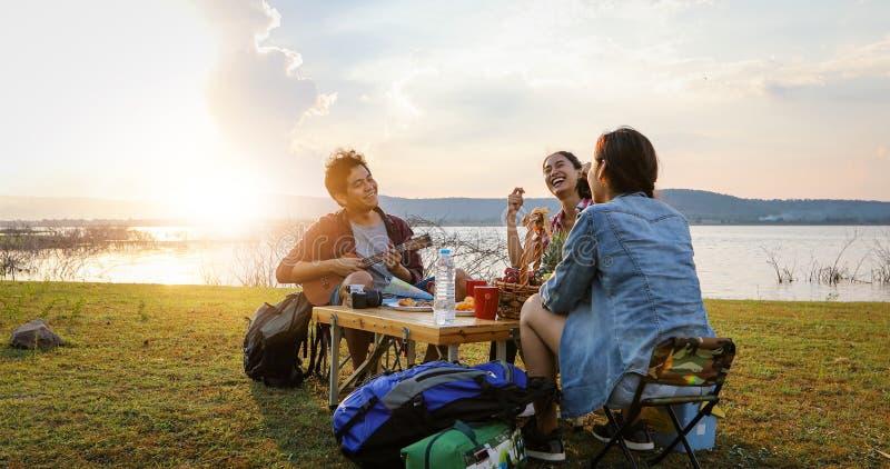Μια ομάδα ασιατικής κατανάλωσης τουριστών φίλων και κιθάρας παιχνιδιού μαζί με την ευτυχία το καλοκαίρι ενώ έχοντας τη στρατοπέδε στοκ φωτογραφία