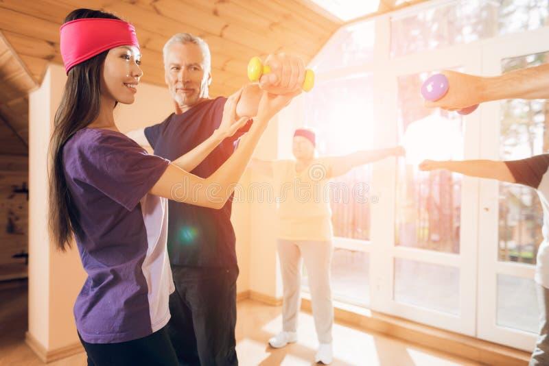 Μια ομάδα ηλικιωμένων γυναικών και ανδρών που κάνουν τη θεραπευτική γυμναστική σε μια ιδιωτική κλινική στοκ εικόνες