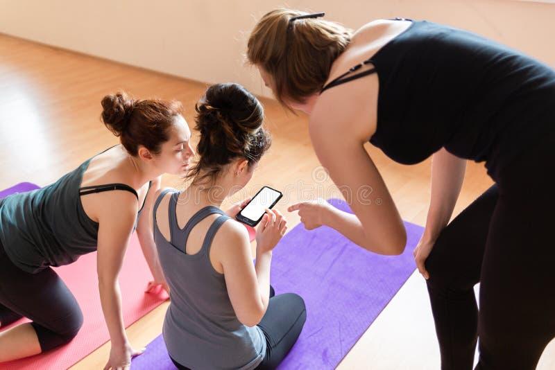 Μια ομάδα νέων γυναικών εξετάζει τις τηλεφωνικές πληροφορίες για την κατάρτιση Τοπ άποψη από την πλάτη Έννοια των σύγχρονων τεχνο στοκ εικόνες