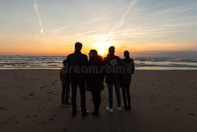 Μια ομάδα νέων εξετάζει το ηλιοβασίλεμα στην παραλία σε Katwijk netherlands στοκ εικόνες