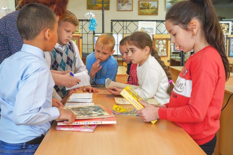 Μια ομάδα νέων μαθητών στέκεται με τα βιβλία στον πίνακα στοκ εικόνες με δικαίωμα ελεύθερης χρήσης