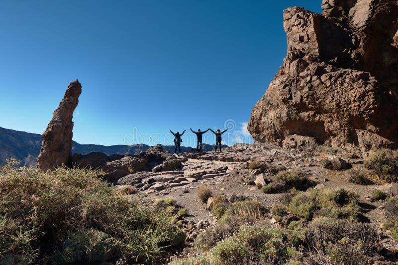 Μια ομάδα νέων που στέκονται κατά τις καλές απόψεις των βουνών Tenerife, Ισπανία στοκ εικόνες