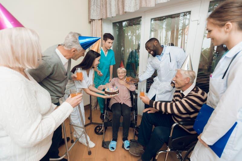 Μια ομάδα νεολαιών και ο ηλικιωμένος άνθρωπος σε μια ιδιωτική κλινική συγχαίρουν μια ηλικιωμένη γυναίκα στα γενέθλιά της στοκ εικόνες