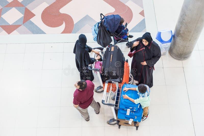 Μια ομάδα οικογένειας της Μέσης Ανατολής περιμένει στον αερολιμένα με lug τους στοκ εικόνα με δικαίωμα ελεύθερης χρήσης