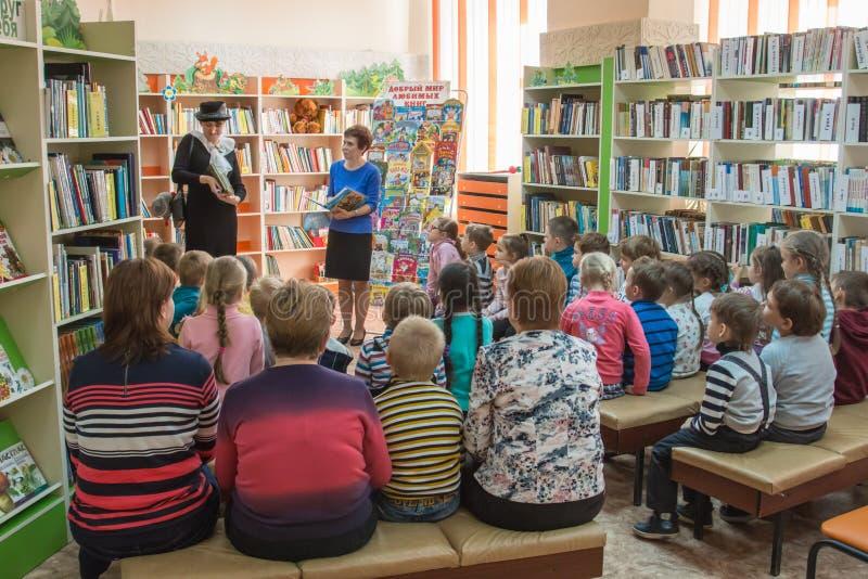 Μια ομάδα παιδιών εκπαιδεύεται στη βιβλιοθήκη στοκ φωτογραφία