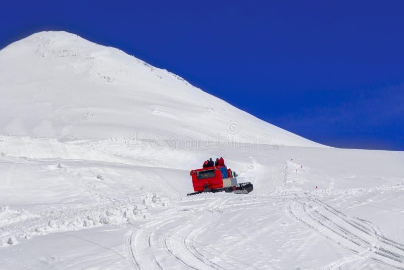 Μια ομάδα τουριστών αναρριχείται σε ένα snowcat σε ένα υποστήριγμα Elbrus στοκ εικόνες