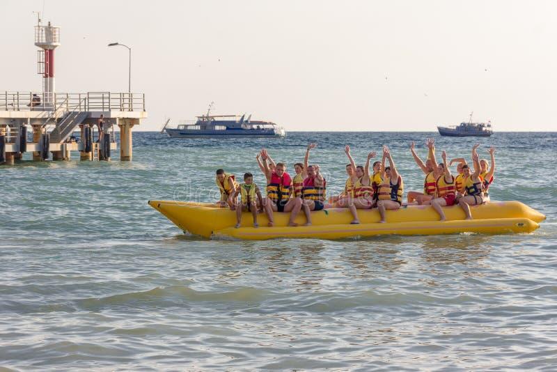 μια ομάδα τουριστών στη συνεδρίαση θάλασσας σε μια διογκώσιμη μπανάνα και τον κυματισμό των χεριών τους στοκ εικόνες