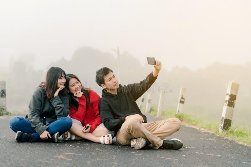 Μια ομάδα τριών ασιατικών φίλων που φορούν ένα πουλόβερ που χρησιμοποιεί ένα τηλέφωνο selfie για να πάρει τις εικόνες σε ένα τουρ στοκ φωτογραφία