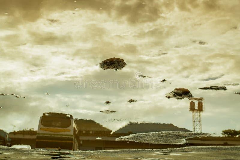 Μια ομάδα των όμβριων υδάτων μετά από ένα ντους βροχής μουσώνα απεικονίζει μια εικόνα του σπιτιού, του λεωφορείου και του σύννεφο στοκ εικόνες