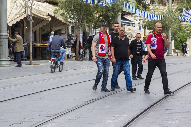 Μια ομάδα υποστηρικτών ομάδων ποδοσφαίρου Hapoel που διασχίζουν την οδό Jaffa στην Ιερουσαλήμ Ισραήλ πριν από την αντιστοιχία του στοκ εικόνα
