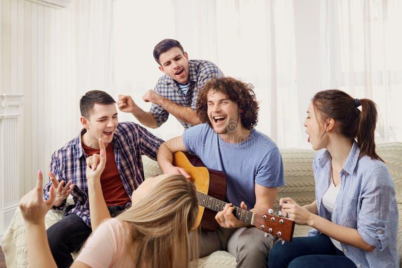 Μια ομάδα φίλων με μια κιθάρα τραγουδά τα τραγούδια σε ένα κόμμα εσωτερικό στοκ εικόνα με δικαίωμα ελεύθερης χρήσης