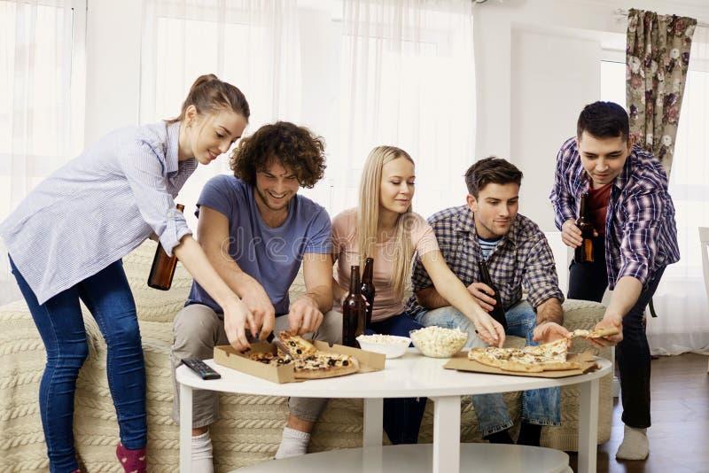 Μια ομάδα φίλων που τρώνε την πίτσα καθμένος στον καναπέ στο θόριο στοκ εικόνες