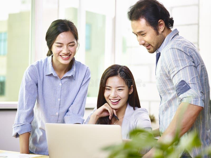 Μια ομάδα της ασιατικής εργασίας επιχειρηματιών μαζί στην αρχή στοκ φωτογραφία με δικαίωμα ελεύθερης χρήσης