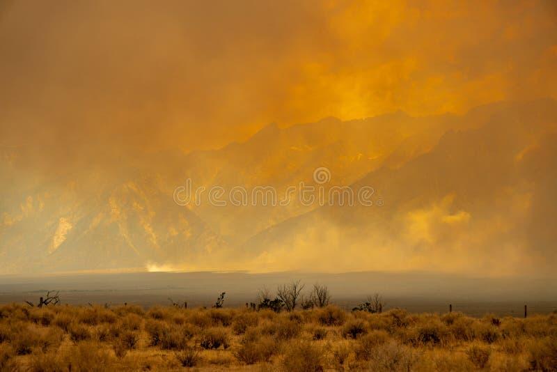 Μια οργιμένος πυρκαγιά σχίζει μέσω της οροσειράς βουνά της Νεβάδας σε Καλιφόρνια, μετατρέποντας τον ουρανό σε φλόγα του πορτοκαλι στοκ φωτογραφίες με δικαίωμα ελεύθερης χρήσης
