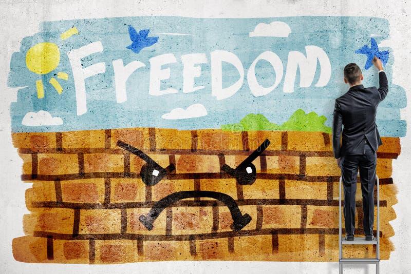 """Μια πίσω άποψη ενός επιχειρηματία που χρωματίζει μια όμορφη ηλιόλουστη ημέρα σε έναν τουβλότοιχο με τη λέξη """"ελευθερία """"ενάντια σ στοκ εικόνα με δικαίωμα ελεύθερης χρήσης"""