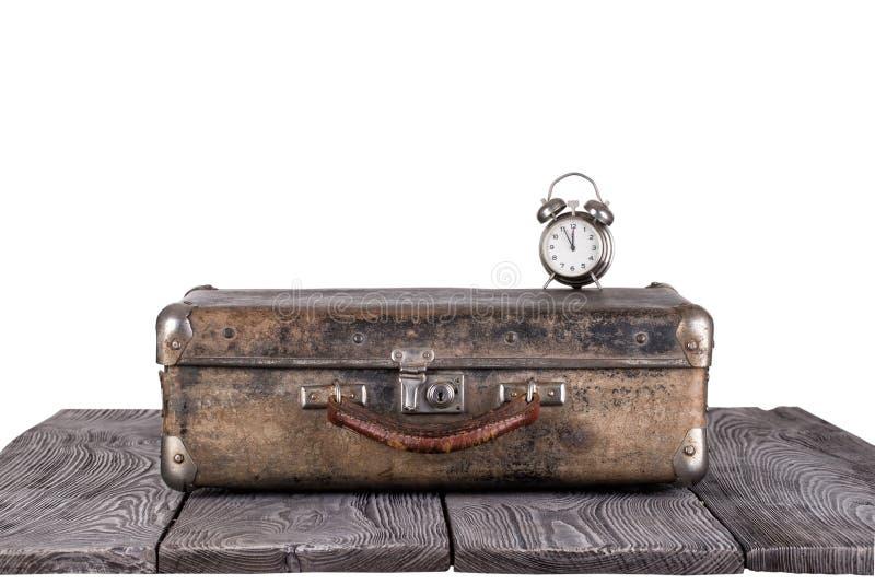 Μια παλαιά βαλίτσα με ένα ξυπνητήρι στους ξύλινους πίνακες στοκ εικόνες