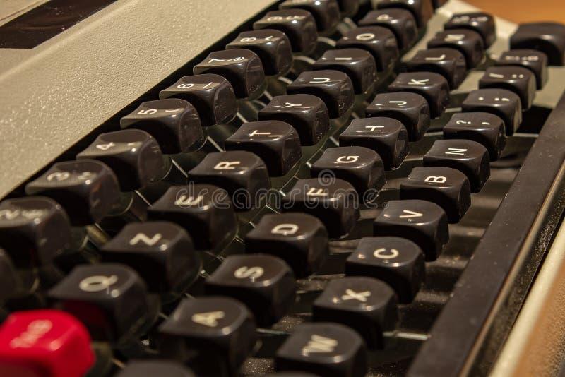 Μια παλαιά γραφομηχανή, με τα κλειδιά και τα όπλα του με τα γράμματα της αλφαβήτου που σύρονται ανωτέρω στοκ φωτογραφία