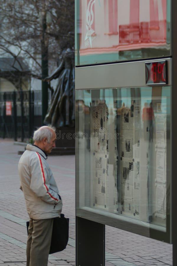 Μια παλαιά εφημερίδα ανάγνωσης ατόμων στην οδό Πληθυσμοί ντόπιων της Μόσχας Ακόμα ζωή στην οδό περπατήματος στοκ φωτογραφία
