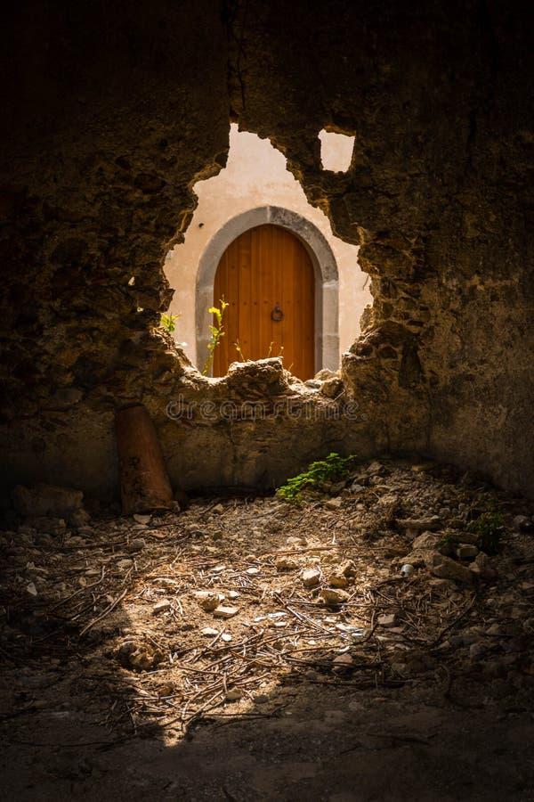 Μια παλαιά ξύλινη σχηματισμένη αψίδα πόρτα στη Σικελία που βλέπει μέσω μιας σπασμένης τρύπας ι στοκ φωτογραφίες με δικαίωμα ελεύθερης χρήσης