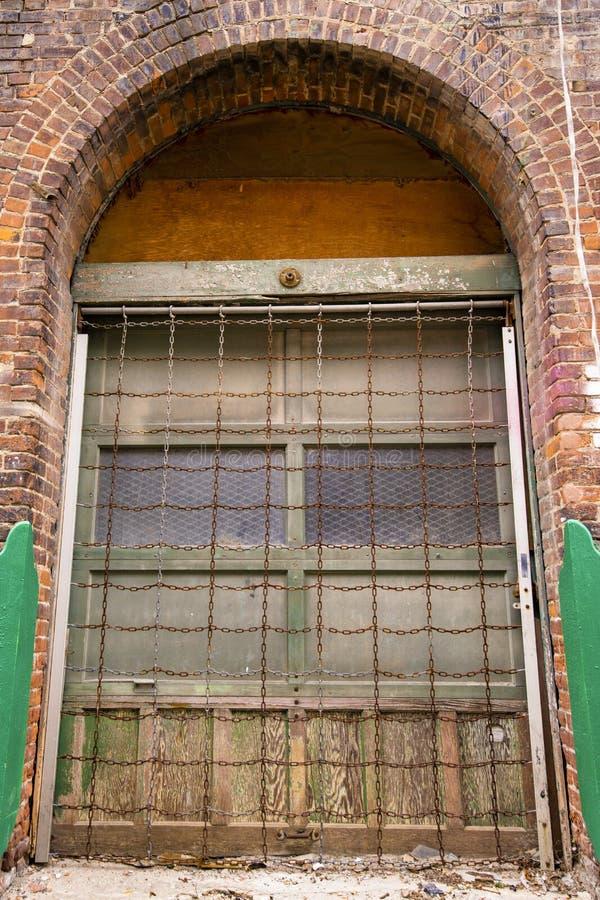 Μια παλαιά σχηματισμένη αψίδα πόρτα σε ένα κτήριο τούβλου στοκ εικόνες