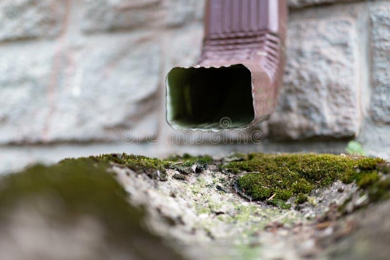 Μια παλαιά υδρορροή σε ένα αποσυνδεμένο σπίτι Αποξήρανση όμβριων υδάτων από τη στέγη στοκ φωτογραφία με δικαίωμα ελεύθερης χρήσης