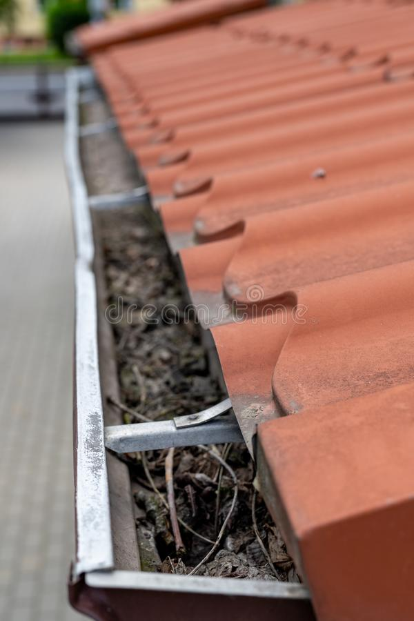 Μια παλαιά υδρορροή σε ένα αποσυνδεμένο σπίτι Αποξήρανση όμβριων υδάτων από τη στέγη στοκ φωτογραφίες
