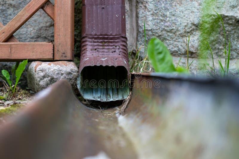 Μια παλαιά υδρορροή σε ένα αποσυνδεμένο σπίτι Αποξήρανση όμβριων υδάτων από τη στέγη στοκ εικόνες