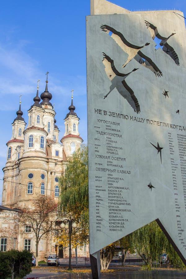 Μια παλαιά όμορφη εκκλησία πίσω από το μνημείο στον παγκόσμιο πόλεμο δύο στο υπόβαθρο του μπλε ουρανού Θρησκευτική αρχιτεκτονική  στοκ εικόνες